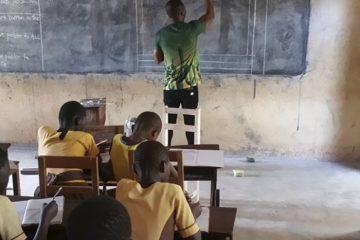 მასწავლებელი თავის მოსწავლეებს კომპიუტერულ პროგრამებს დაფაზე ხატვით ასწავლის
